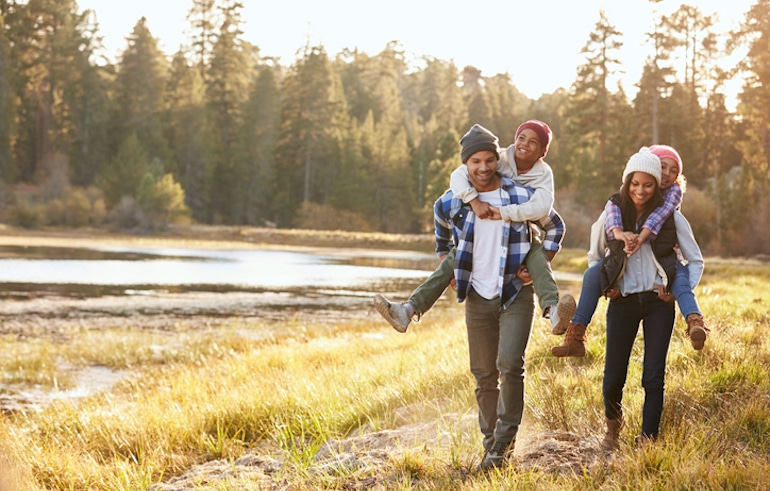 Family of four walking in nature to experience the calming health benefits