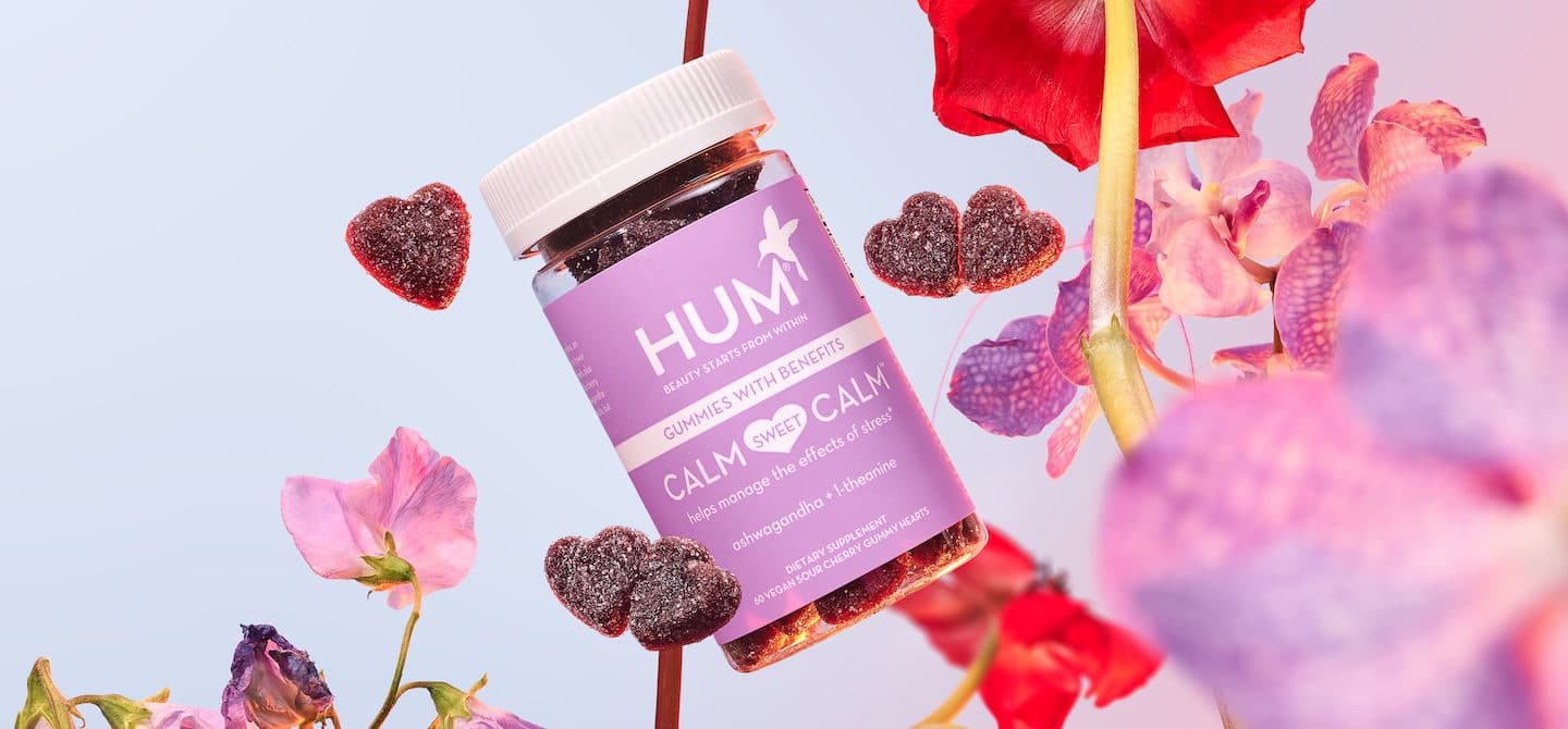 HUM Calm Sweet Calm stress gummies with flowers in front of a lilac background