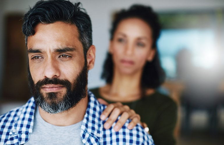 Woman comforting distraught husband over erectile dysfunction from as a hormone imbalance symptom