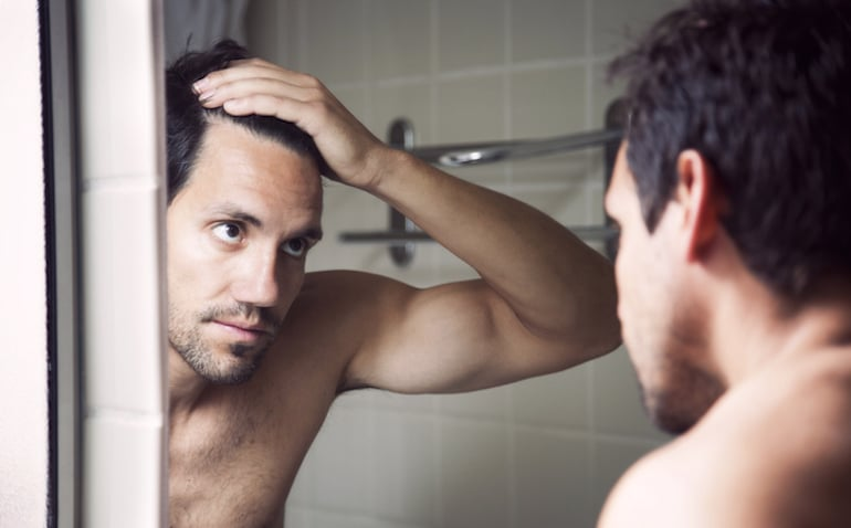 Man checking hair line in the mirror to investigate hair loss
