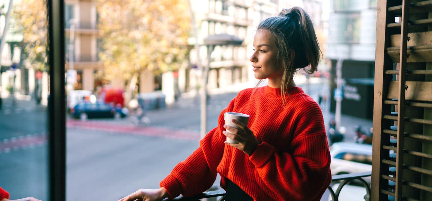 Woman enjoying coffee on her balcony, observing nature and the benefits of staying present