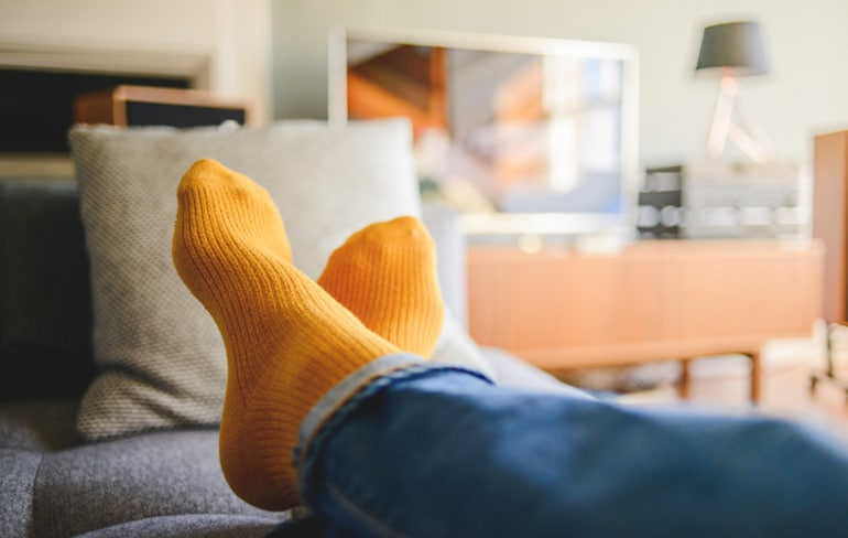 Shot of person's feet up on couch to illustrate staying present by taking breaks