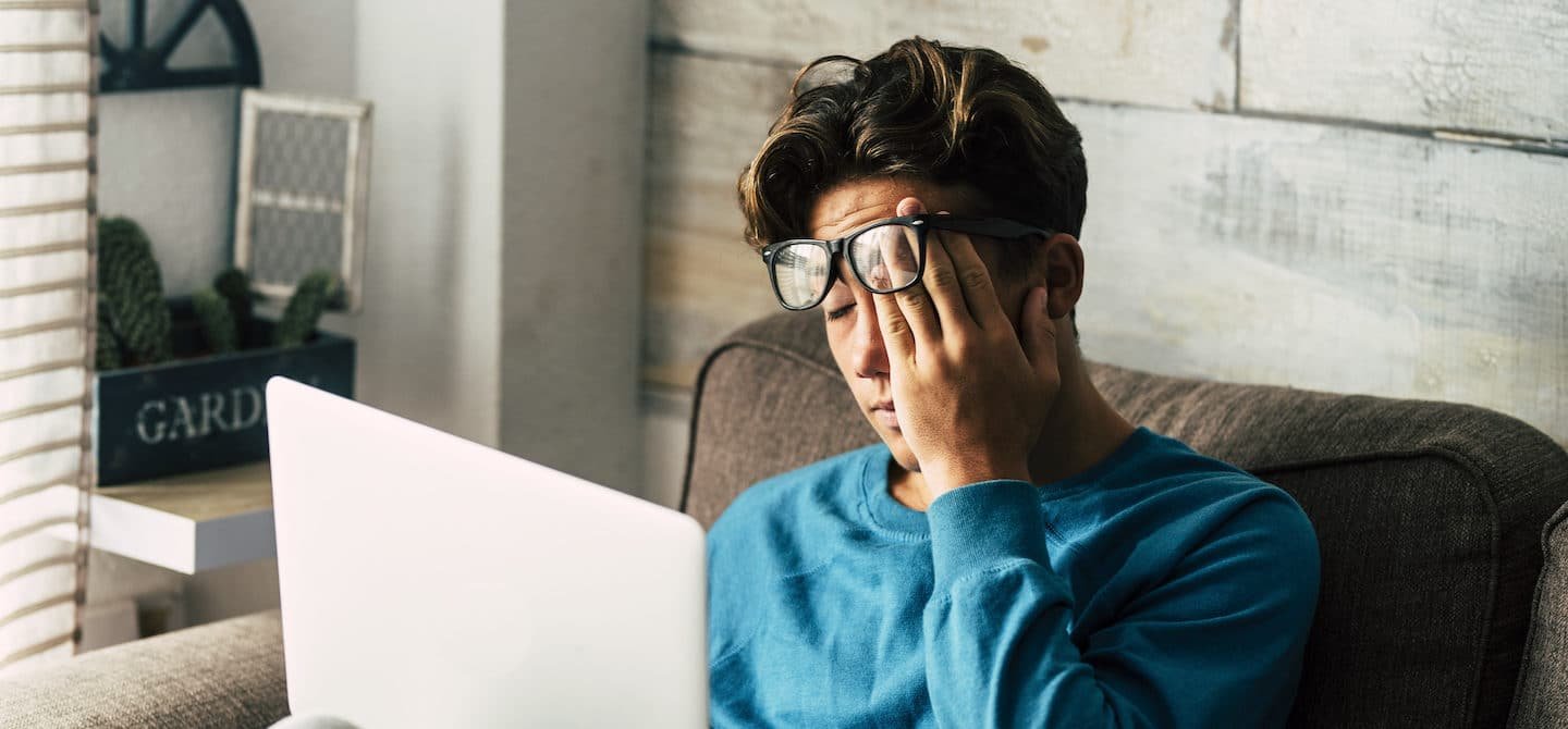 Fatigued man experiencing fatigue from hormonal imbalance at home on his laptop