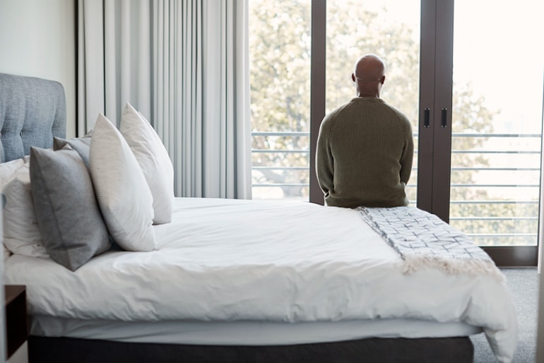 Man sitting on bed looking outside, tired from symptoms of male hormonal imbalance