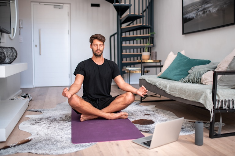 Man meditating and doing breathwork at home, a key skill to learn on how to be present