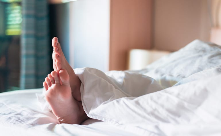 Person's foot under weighted blanket in bed to reap benefits for stress and sleep