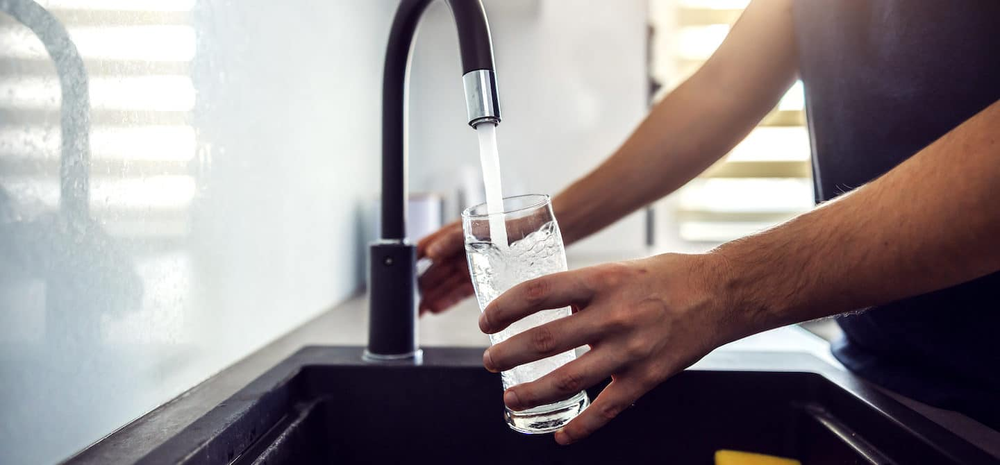 Close up of man getting a glass of water from the kitchen sink since he knows it's important to stay hydrated