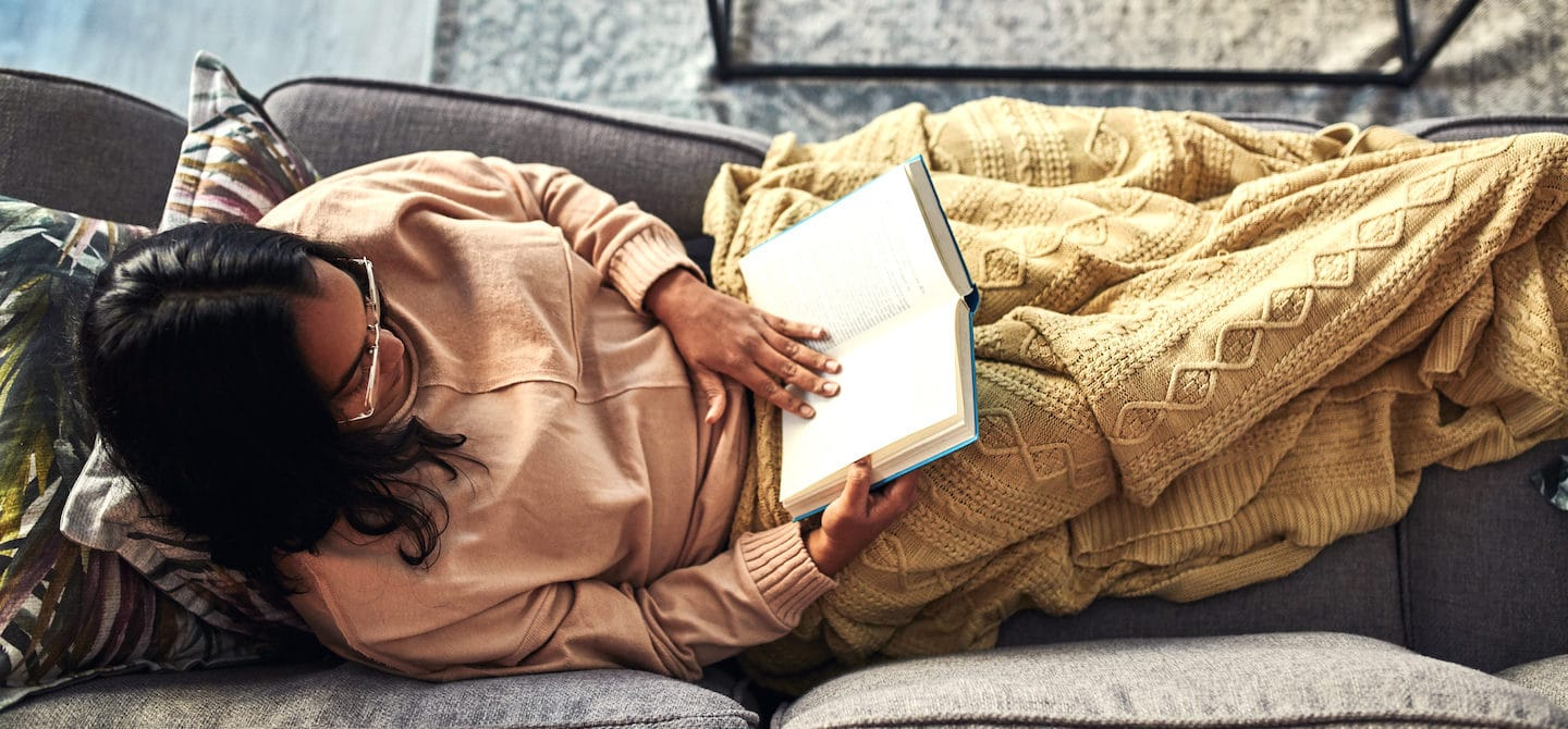 Woman reading a book on the couch as a stress reduction technique