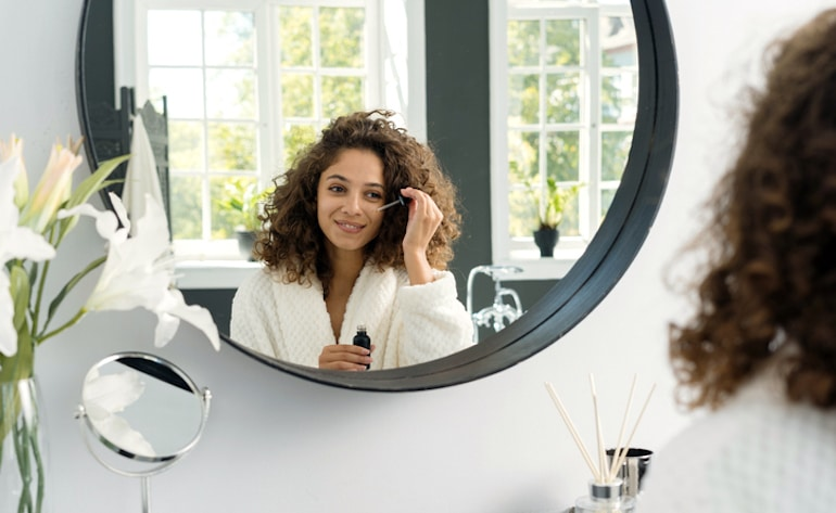 Woman applying hyaluronic acid serum, one of the best ingredients for dry skin, while looking in the mirror