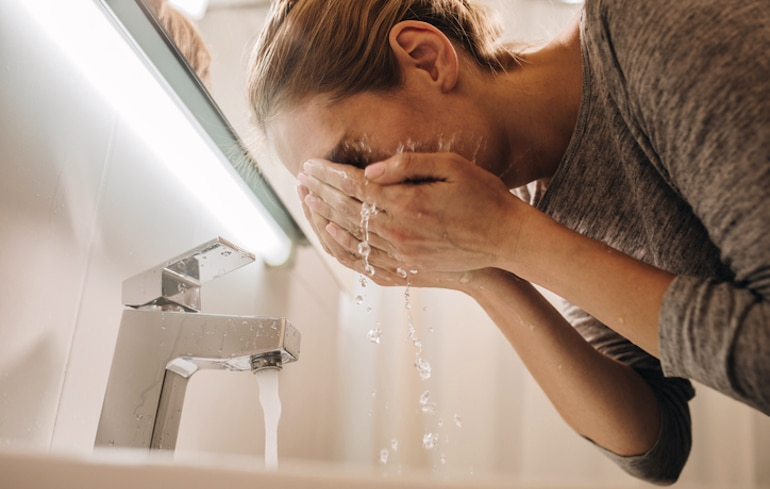 Woman washing her face with gentle glycolic and lactic acids