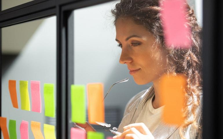 Mujer que usa notas adhesivas en la pared para planificar buenos hábitos de éxito