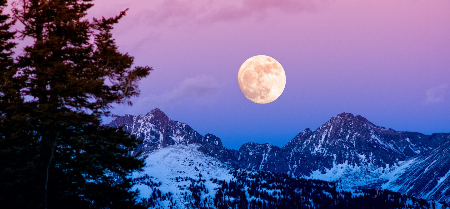 Beautiful winter night sky of purple, pink, and blue hues with a full moon