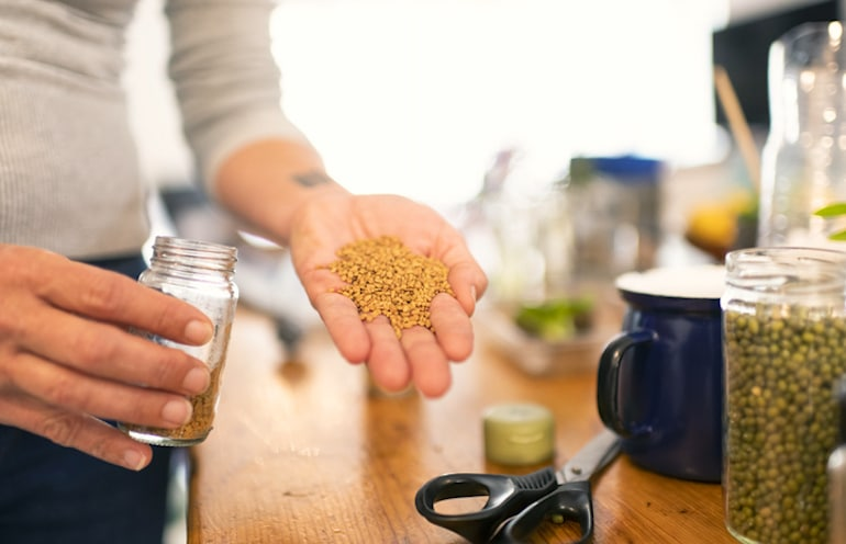 Woman holding fenugreek seeds to add to her diet for its libido-boosting effects
