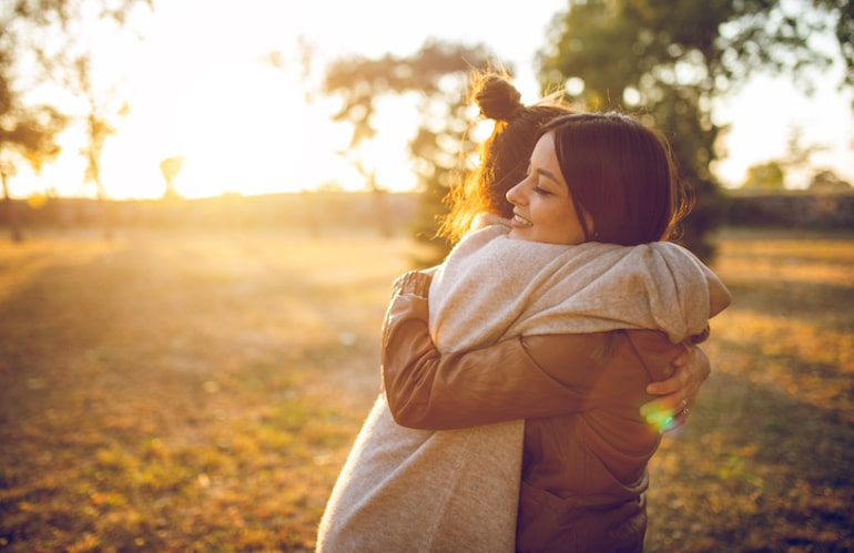 Friends hugging outdoors, showing support helps reduce stress