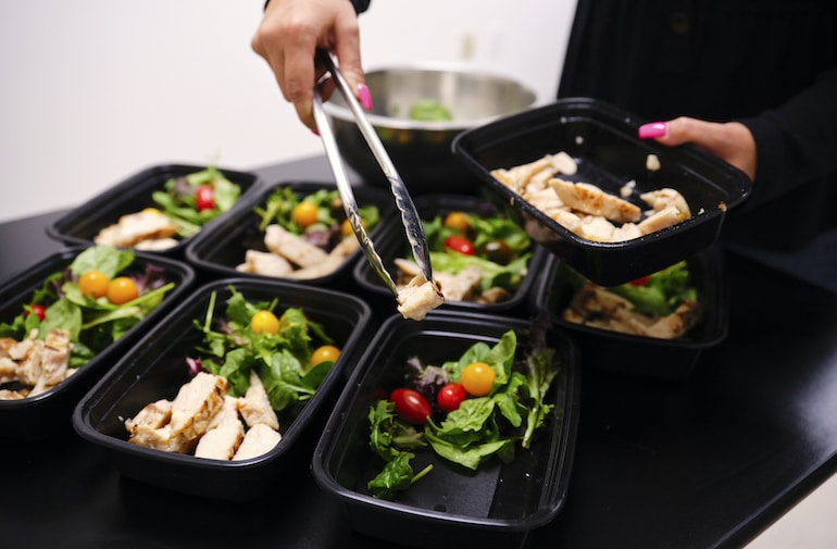 Woman meal prepping healthy salads with chicken to establish good nutrition habits