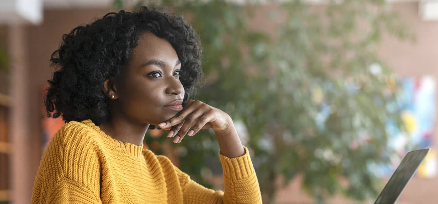 Pensive woman sitting at desk, wondering how long it takes to build a habit