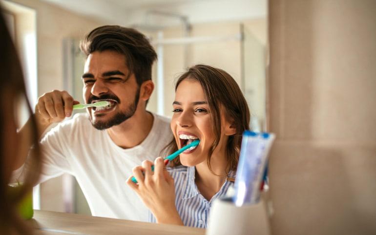 Pareja cepillándose los dientes juntos: un ejemplo de cómo los hábitos inconscientes pueden ser beneficiosos