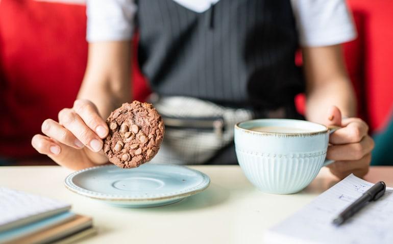 Mujer tomando una galleta con café, un hábito que debes cambiar si quieres comer más sano
