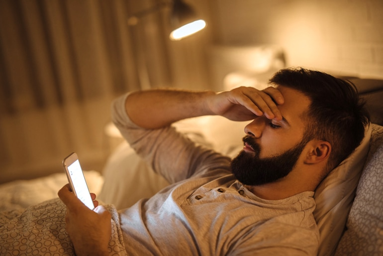 Man worrying in bed on his phone, recognizing triggers in order to create good habits