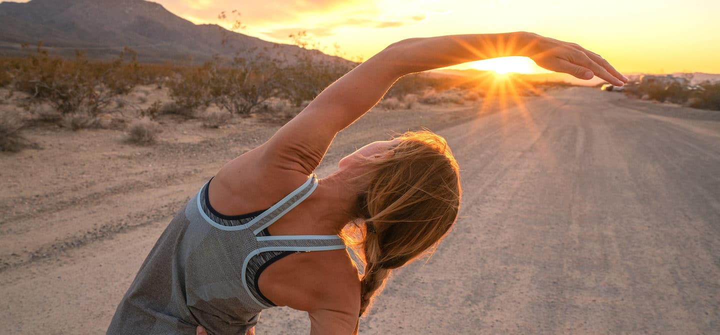 Woman stretching at sunset, with working out as her goal to form badass habits