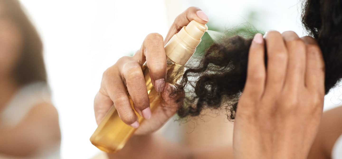 Woman spraying oil onto her ends to perfect her curly hair wash day routine