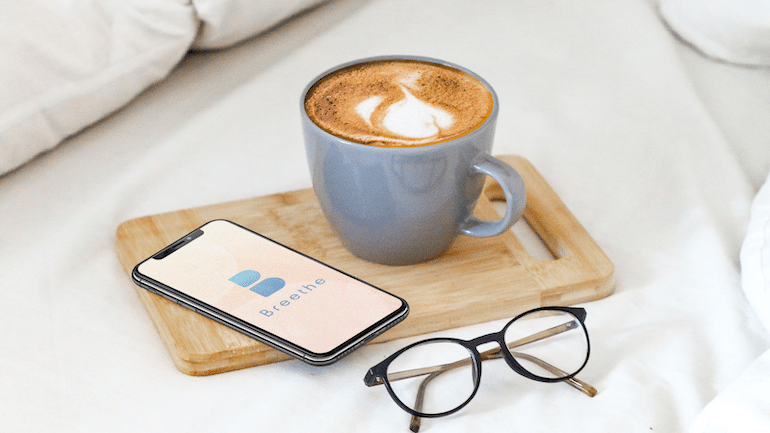 Phone with the Breethe meditation app, cup of coffee, and glasses on a bed