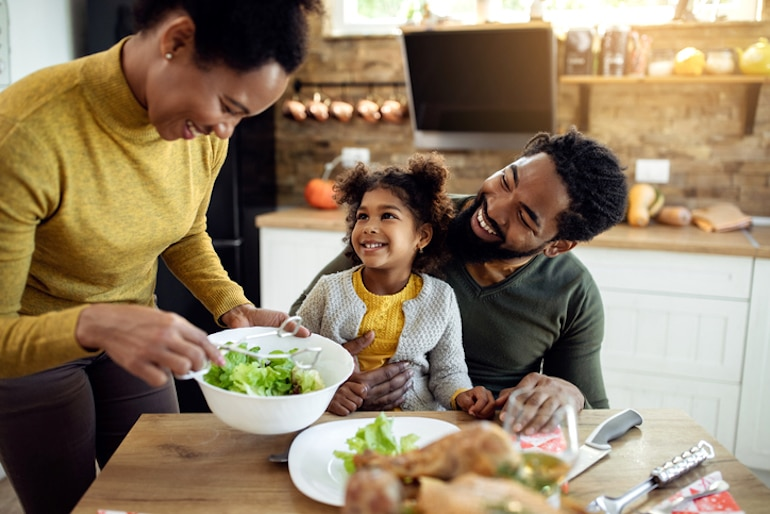 Family of three enjoying dinner, mindful eating, and other benefits of self-care with food and relationships