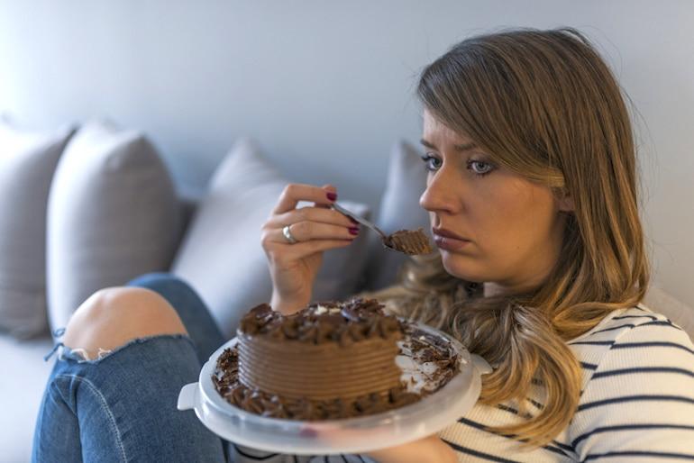 Mujer estresada triste comiendo un pastel solo