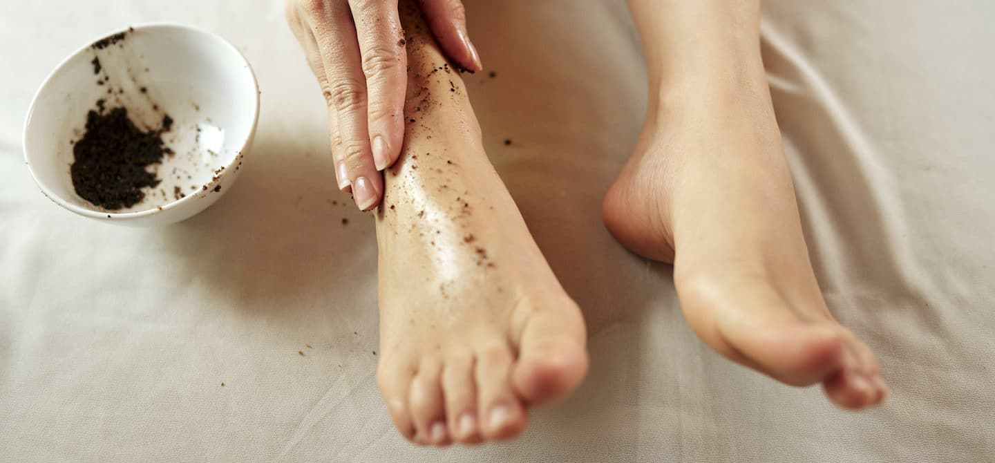 Woman exfoliating her dry, cracked feet with an exfoliating scrub