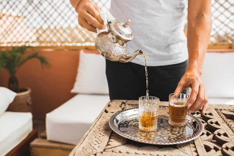 Man pouring Moroccan tea to help meet his hydration quota for the day