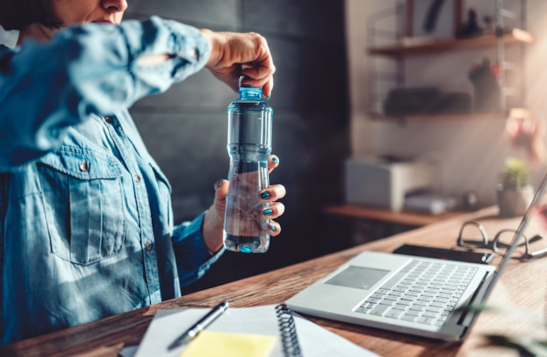 Woman opening bottle of water at her desk, since hydrating can improve your focus at work and prevent side effects of dehydration; a reason why it's important to stay hydrated