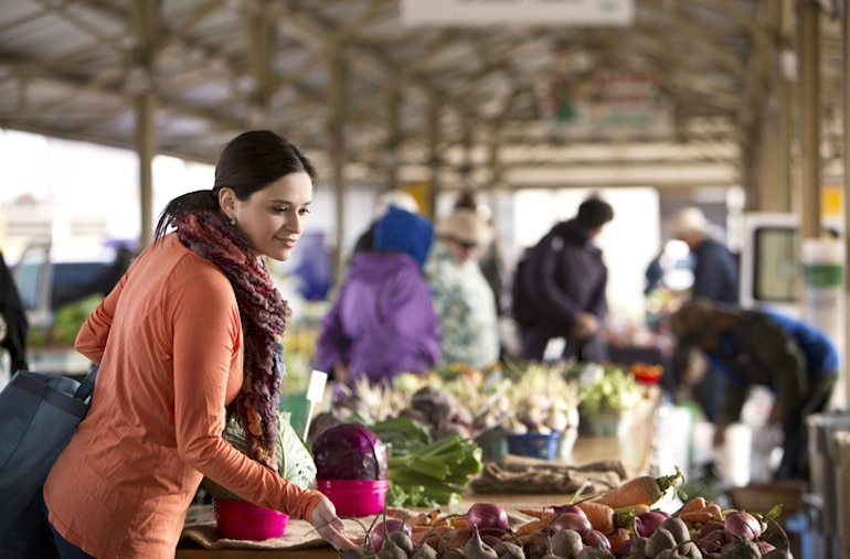 Woman buying fresh seasonal produce at farmers market