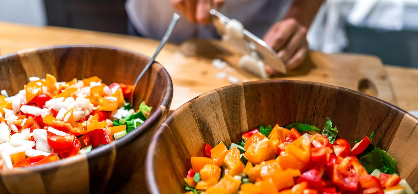 Man chopping vegetables for a low-fat diet salad, which may lead to unwanted side effects like cravings and mood imbalances