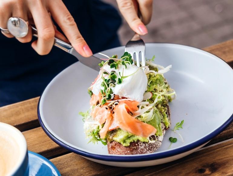 Mujer rebanando tostadas de salmón y aguacate con huevo escalfado, comida saludable rica en grasas que tiene muchos beneficios para la salud y la belleza