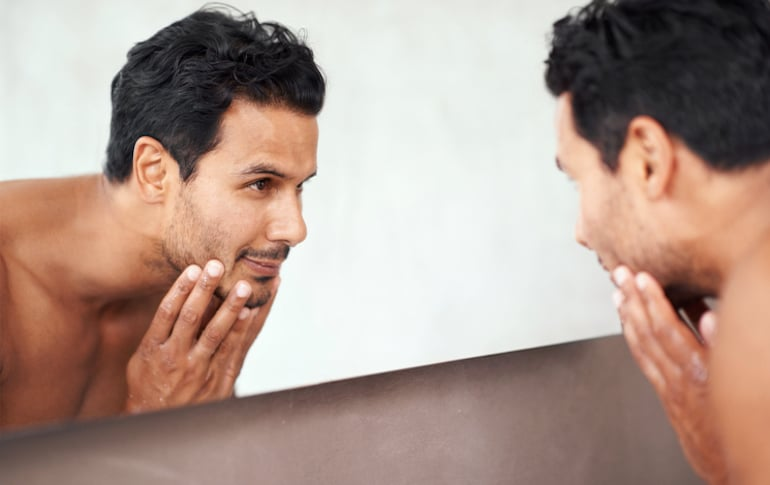 Hombre guapo mirando en el espejo admirando su tez después de usar té verde productos para el cuidado de la piel para aclarar e hidratar