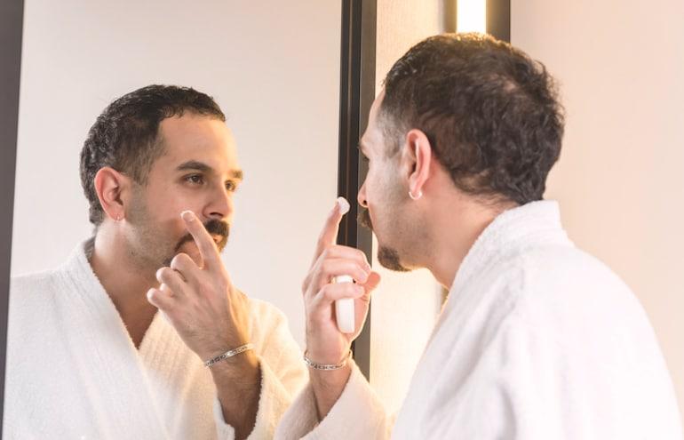Hombre aplicar tratamiento para el acné en el espejo para deshacerse de las espinillas ciegas