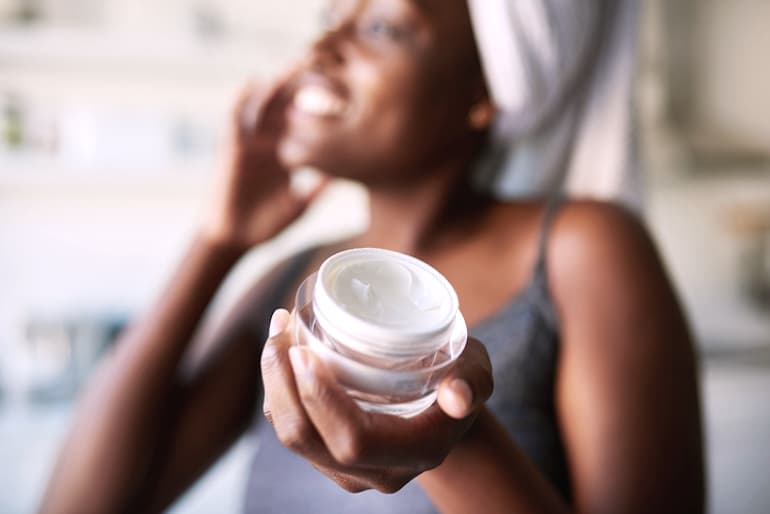 Woman using exfoliating topical products to treat and heal her acne scars