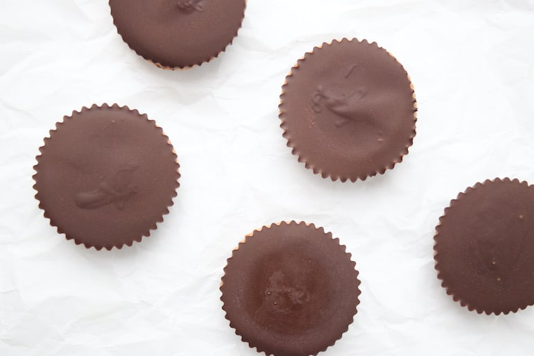 Overhead shot of dark chocolate almond butter cups neatly arranged on a kitchen counter