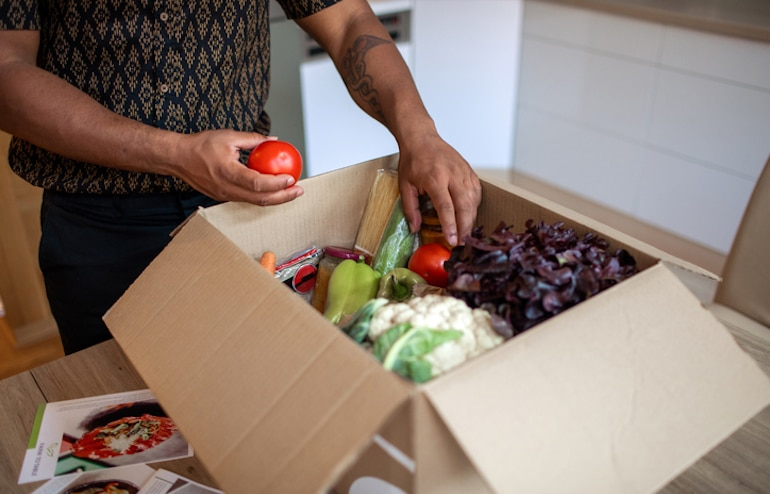 Man unpacking healthy grocery deliver as a strategy to stop late-night snacking