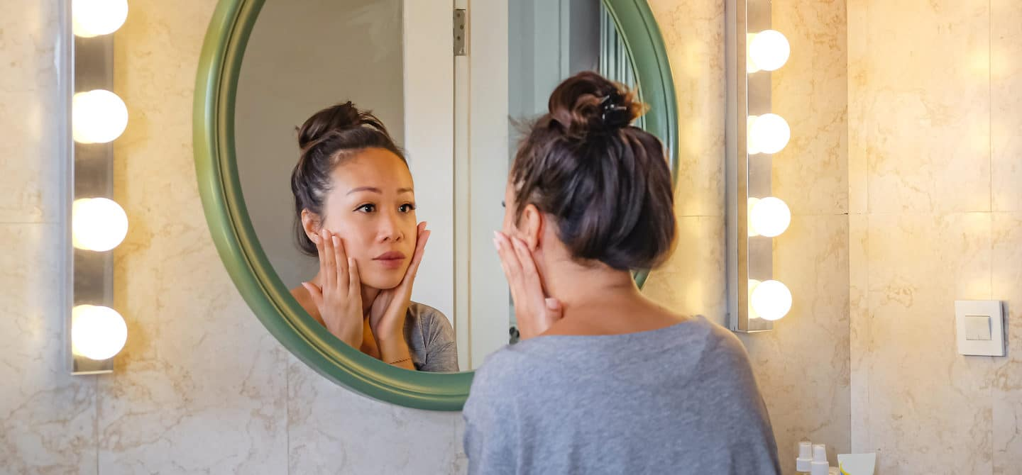 Worried woman looking at her face in the mirror and investigating skin purging from a new product