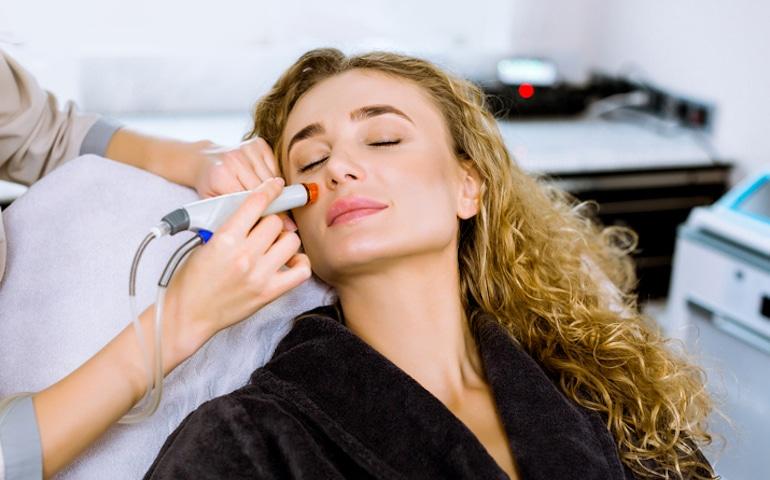 Mujer recibiendo HydraFacial en el consultorio del dermatólogo para tratar las espinillas ciegas