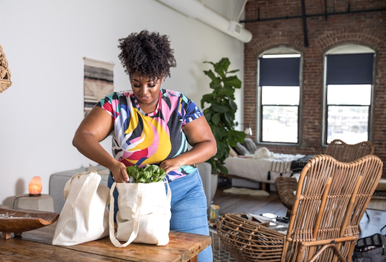 Woman unpacking her grocery bags with Flexitarian Diet staples like veggies and plant-based protein