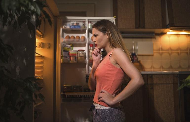 Mujer hambrienta mirando en el refrigerador por la noche, que tiene antojos de 24 horas como efecto secundario de una dieta baja en grasas