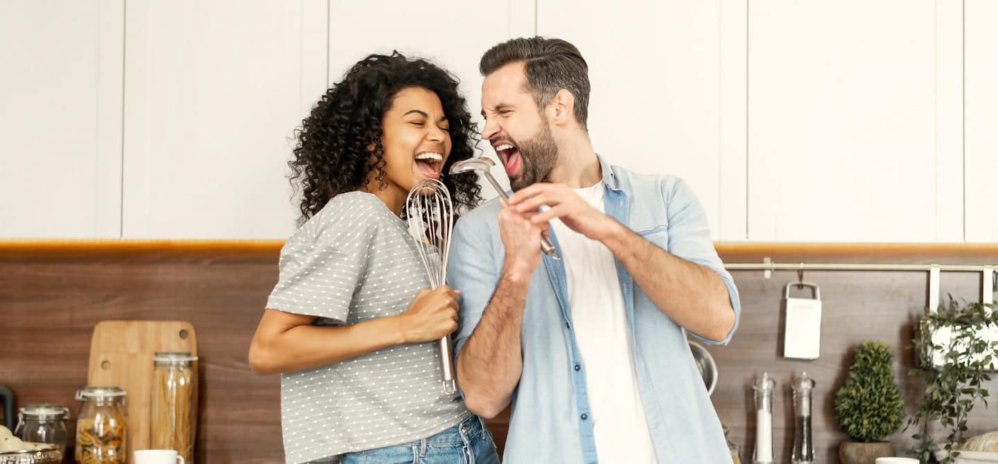 Couple happily singing in the kitchen, demonstrating the benefits of listening to music for your health and relationships