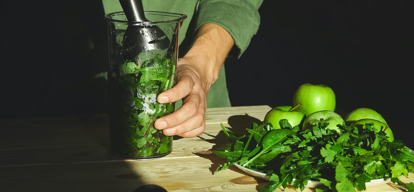 Man mixing a smoothie with various types of leafy greens to reap their health benefits