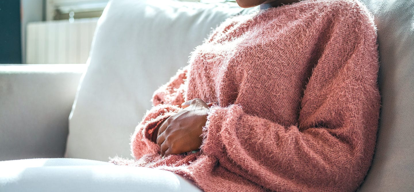 Woman clutching her stomach in pain because she's menstruating and suffering from the pains of period poops