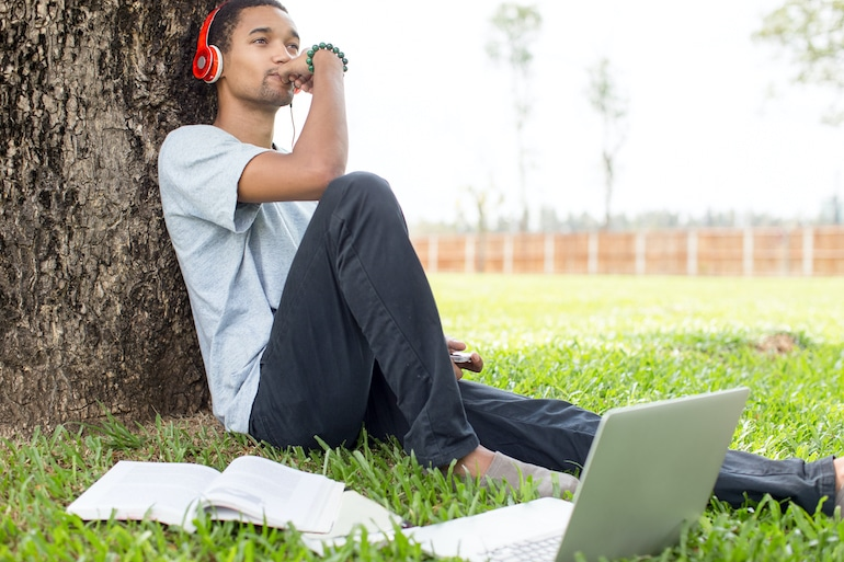 Man listening to music to benefit from productivity and creativity while working on laptop outdoors