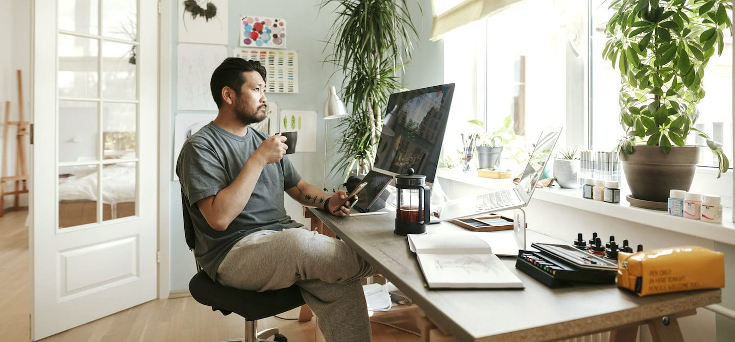 Man drinking French press coffee at his desk, wondering if coffee makes you bloated