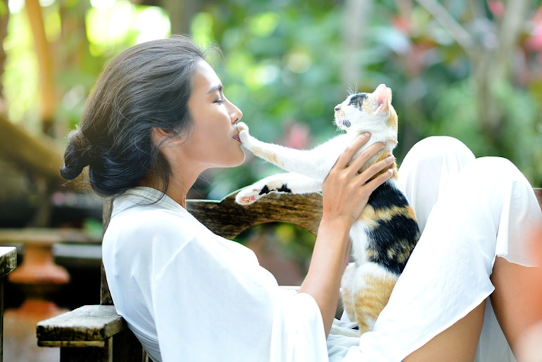 Woman outside kissing her cat's paw to show affection and health benefits of pets