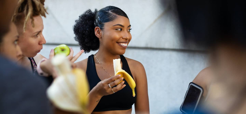 Woman eating a banana as a post workout food
